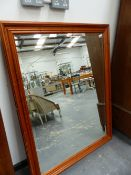 A LARGE PINE FRAMED MIRROR.