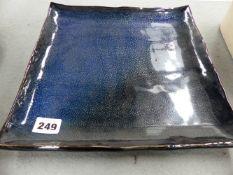 A STUDIO POTTERY CHARGER OF SQUARE FORM.