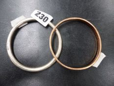 A 9ct. GOLD BANGLE TOGETHER WITH A HALLMARKED SILVER BANGLE.