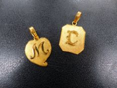 TWO 22ct INITIAL PENDANTS.