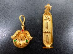 A YELLOW METAL CARTOUCHE PENDANT TOGETHER WITH ONE OTHER.