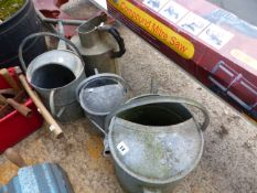 FOUR GALVANISED WATERING CANS.