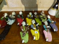 A SET OF HAND CARVED AND PAINTED ORIENTAL WALL HANGING MUSICIAN FIGURES.