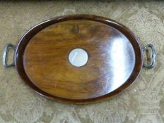 AN OVAL WALNUT SILVER MOUNTED TWO HANDLED ART DECO TRAY. APPROXIMATE MEASUREMENT 59.5cms x 37cms.