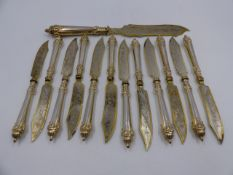 A SET OF TWELVE WHITE METAL FISH KNIVES AND A LARGER SERVING KNIFE WITH GILDED EDGES AND ENGRAVED