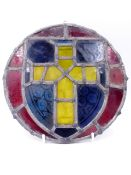 AN ANTIQUE STAINED GLASS ROUNDEL OF A CROSS WITHIN A SHIELD. D.24cms.