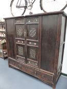 AN IMPRESSIVE CHINESE CARVED CABINET WITH TWO PIERCED PANEL DOORS ABOVE THREE BASE DRAWERS. H.166