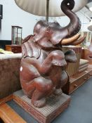 A PAIR OF EASTERN CARVED HARDWOOD FIGURES OF SEATED ELEPHANTS NOW MOUNTED AS LAMPS. OVERALL H.