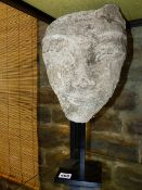 AN ORIENTAL STUCCO FRAGMENT OF A DEITY'S FACE ON MUSEUM TYPE METAL BASE. OVERALL H.44cms.