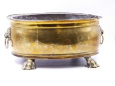 A 19th.C.BRASS OVAL JARDINIERE/COOLER WITH LION MASK HANDLES, PAW FEET AND TOLE LINER. W.36cms.