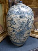 A LARGE CHINESE PROVINCIAL POTTERY OVOID FORM JAR AND COVER DECORATED IN BLUE WITH PANELS OF