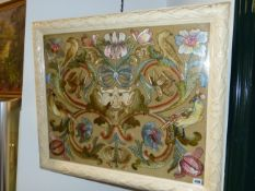 AN ARTS AND CRAFTS SILKWORK PANEL OF BIRDS AND FLOWERS SURROUNDING A MASK IN CARVED AND LATER