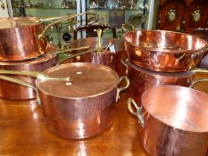 A POLISHED COPPER AND BRASS ANTIQUE AND LATER PART BATTERIE DE CUISINE TO INCLUDE FOUR LARGE COVERED