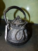 A JAPANESE CEREMONIAL IRON TEAPOT OF GLOBULAR FORM WITH BROCADE TIES AND KNOTS. H.OVER HANDLE