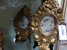 A PAIR OF ITALIAN GILTWOOD CARVED ROCOCO STYLE OVAL SMALL FRAMES WITH INSET PANELS OF FLORAL
