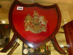 A GOLD AND SILVER THREAD EMBROIDERED ROYAL ARMS IN A SHIELD SHAPE FRAME.