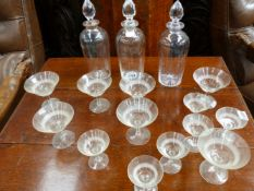 THREE CRYSTAL DECANTERS WITH CUT GLASS STOPPERS AND TWO SETS OF SIX WINE GLASSES. (15)