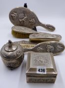 SEVEN ASIAN WHITE METAL DRESSING TABLE PIECES EACH WITH FIGURAL DECORATION TO INCLUDE A HAND MIRROR,