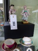 TWO POLYCHROME PORCELAIN FIGURES OF A BOY AND GIRL IN THE MANNER OF MEISSEN AND TWO MINIATURE CUPS