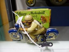 A SCHUCCO TINPLATE CLOCKWORK TOY MOTORCYCLE AND RIDER, PATENT MOTO-DRILL 1006. COMPLETE WITH BOX.