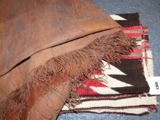 AN AMERICAN INDIAN NAVAJO FLATWEAVE RUG OF GEOMETRIC DESIGN 121 x 79cms AND A LEATHER PATCHWORK