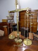 A LARGE SET OF BRASS SHOP BEAM SCALES WITH BULL'S HEAD FINIALS, TWIN PANS AND SHAPED BASE WITH