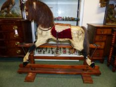 AN EARLY 20th.C.CARVED WOOD AND PAINTED ROCKING HORSE ON TRESTLE BASE. 91cms (HOOF TO EAR)