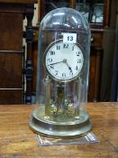 AN EARLY 20th.C.ANNIVERSARY CLOCK UNDER GLASS DOME. H.33cms.