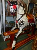 AN EARLY 20th.C.CARVED AND PAINTED WOOD ROCKING HORSE ON TRESTLE BASE. 92cms (HOOF TO EAR)