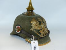 A GERMAN PICKLEHAUBE HELMET WITH GREEN CLOTH SKULL AND SPIKE FINIAL.