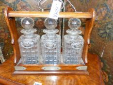 A LATE VICTORIAN OAK THREE BOTTLE LOCKING TANTALUS TOGETHER WITH THREE HALLMARKED SILVER SPIRIT