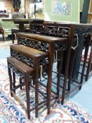 A NEST OF FOUR CHINESE CARVED HARDWOOD TABLES WITH PIERCED FOLIATE APRONS.