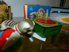 A GNK WEST GERMAN TINPLATE CLOCKWORK CAT AND BALL TOY COMPLETE WITH CARD BOX TOGETHER WITH AN