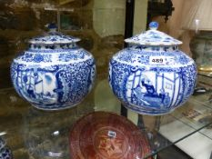 A NEAR PAIR OF CHINESE BLUE AND WHITE COVERED JARS WITH FIGURAL PANELS SURROUNDED BY SCROLLING