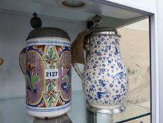 TWO ANTIQUE PEWTER MOUNTED DELFT TANKARDS.