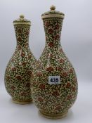 A PAIR OF EASTERN POTTERY BOTTLE FORM COVERED VASES WITH OVERALL FLORAL AND FOLIATE DECORATION. H.