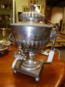 A 19TH CENTURY SHEFFIELD PLATED TEA URN ON SQUARE FORM BASE AND BUN FEET AND WITH LION MASK RING