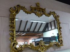AN ANTIQUE CARVED GILTWOOD MIRROR IN THE CHIPPENDALE MANNER. W.110 x H.95cms.