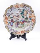 A CHINESE EXPORT FAMILLE ROSE PLATE WITH MANDARIN FIGURAL DECORATION AND LANDSCAPE PANELS TO THE