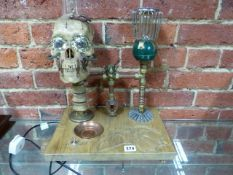 AN UNUSUAL STEAM PUNK THEMED DESK LAMP WITH CARVED BASE AND ILLUMINATING SKULL.
