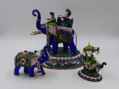 THREE INDIAN ENAMEL AND SILVERED FIGURES OF ELEPHANTS, TWO WITH HOWDAHS AND RIDERS. LARGEST H.16.