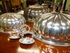 A GRADUATED SET OF THREE 19th.C.SILVER PLATED MEAT COVERS OF MELON FORM WITH DETACHABLE HANDLES.