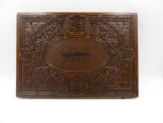 AN EASTERN CARVED SHALLOW DOCUMENT BOX, THE TOP DECORATED WITH STYLISED CALLIGRAPHY. W.36cms.