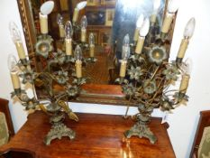 A PAIR OF ANTIQUE FRENCH BRASS TABLE CANDELABRA WITH STYLISED FLOWER HEAD DECORATION FITTED AS