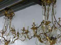 AN IMPRESSIVE PAIR OF GILT BRASS CAGE CHANDELIERS HUNG WITH LARGE CUT GLASS AND FACET DROPS. H.