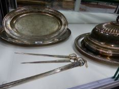 A SMALL SILVER PLATED MEAT COVER, THREE SERVING TRAYS AND FOUR SKEWERS.
