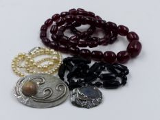 A GRADUATED ROW OF CHERRY RED ,POSSIBLY AMBER, BEADS TOGETHER WITH TWO FURTHER NECKLETS AND TWO BROO