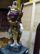 A CARVED AND DECORATED INDONESIAN FIGURE OF A MYTHICAL WARRIOR HOLDING A SWORD. H.61cms.
