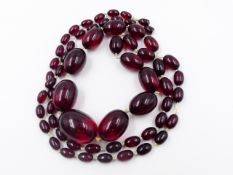 A GRADUATED ROW OF OVAL CHERRY AMBER BEADS. APPROXIMATE WEIGHT 113grms.