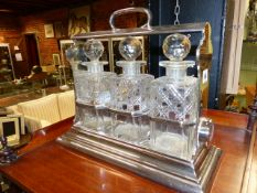 AN EDWARDIAN SILVER PLATED THREE BOTTLE TANTALUS BY WALKER & HALL.
